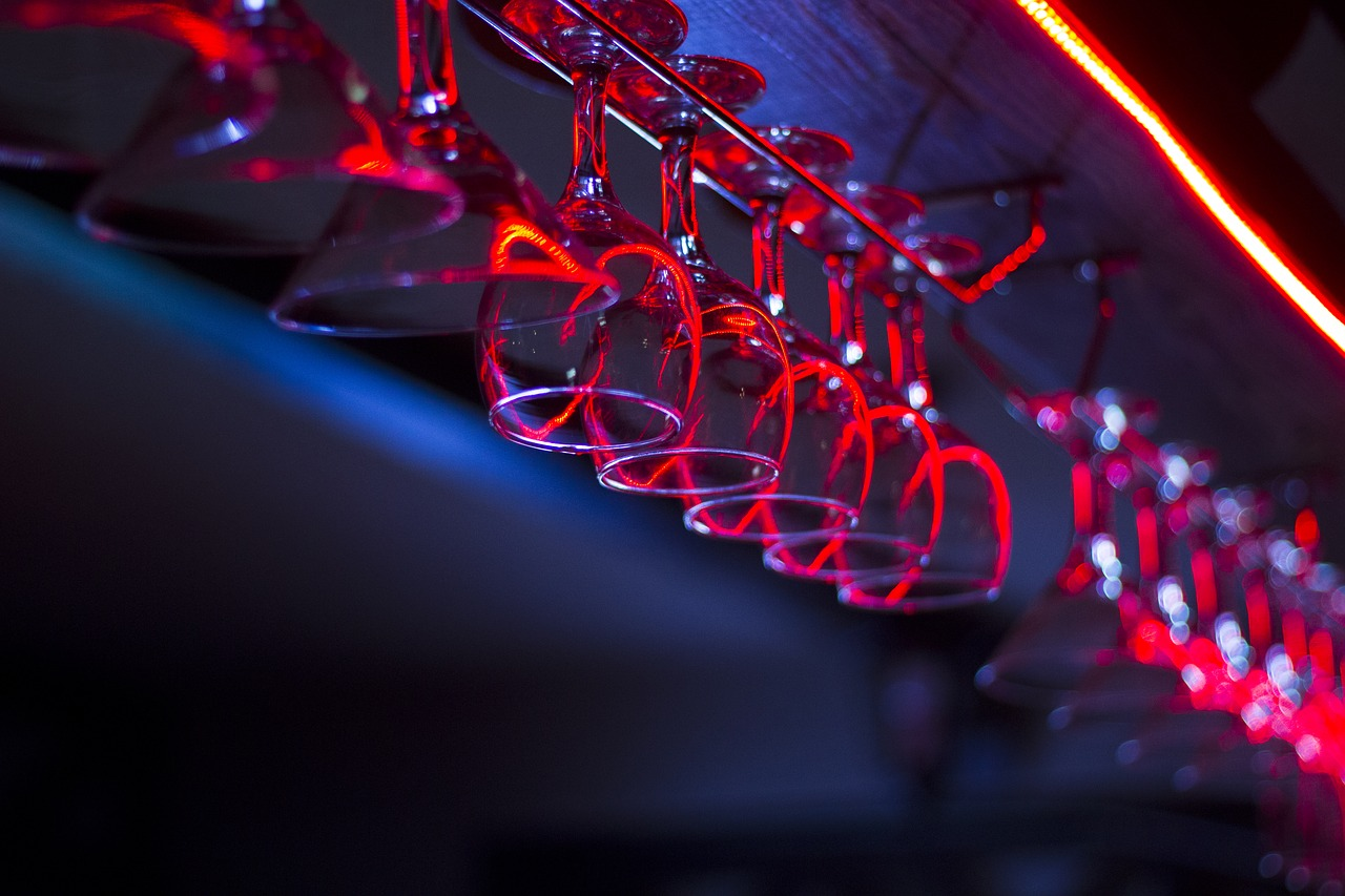 Wine glasses hanging upside down in a bar bathed in red and blue lights
