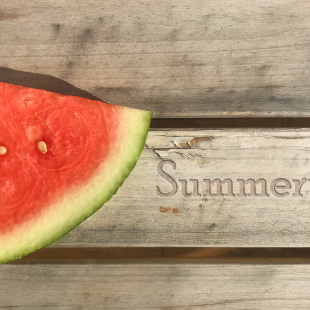 "A slice of watermelon on a wooden table with the word ""Summertime"" seemingly carved into it"