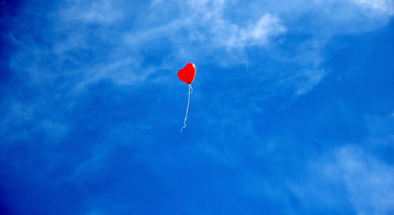 A single red heart-shaped balloon with a white spring floats away against a blue sky with a few thin clouds.